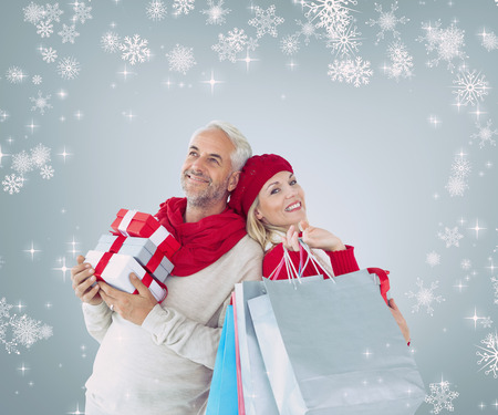 Happy festive couple with gifts and bags against grey vignette photo