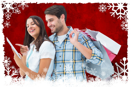 Happy couple with shopping bags and tablet against christmas themed snow flake frame photo