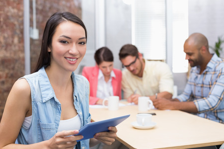 Smiling woman holding tablet in front of her colleague in the office photo