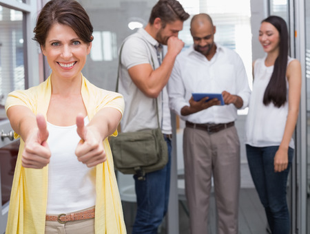 Woman giving thumbs up at camera in front of her colleagues in the office photo