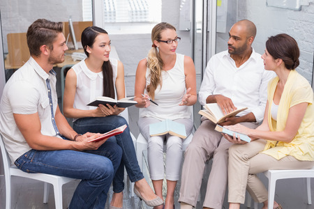 book club: Business team talking about their books in the office Stock Photo