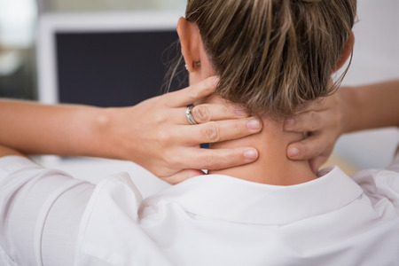 pain: Close up mid section of businesswoman suffering from neck ache in office