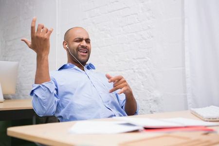 air guitar: Happy young businessman listening music while playing air guitar in office