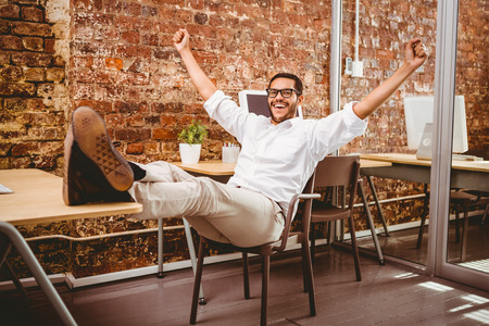Portrait of cheerful businessman cheering in the office photo