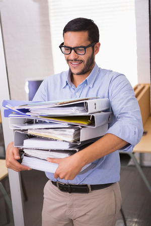 Young businessman carrying stack of folders in office photo