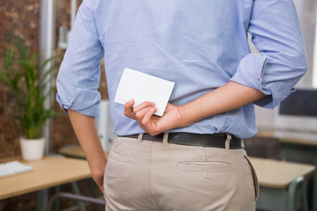 Close up mid section of man holding blank business card behind his back photo