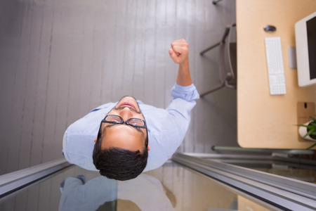 High angle view of cheerful businessman cheering in the office photo