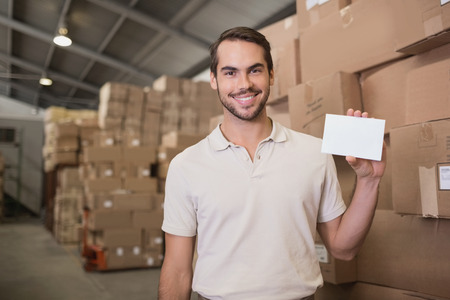 Portrait of warehouse worker holding blank paper in warehouse photo