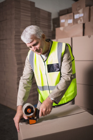 sealing tape: Worker in warehouse preparing goods for dispatch