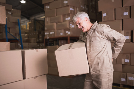 storage boxes: Side view of worker with backache while lifting box in the warehouse
