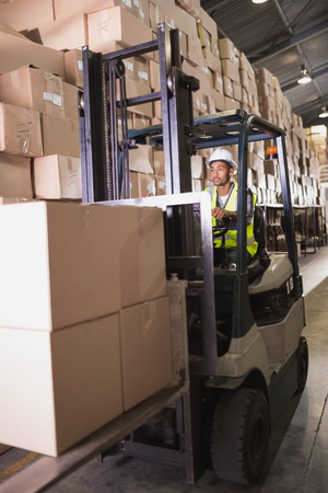 Driver operating forklift machine in warehouse photo