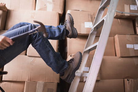 accident at work: Low section of worker falling off ladder in the warehouse Stock Photo