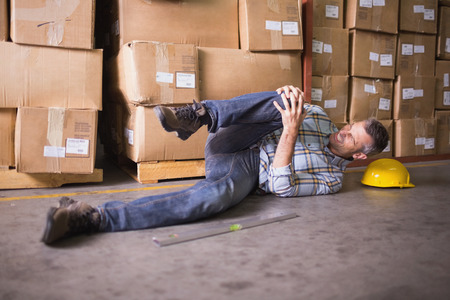 accidente trabajo: Vista lateral del trabajador de sexo masculino tendido en el piso en el almacén