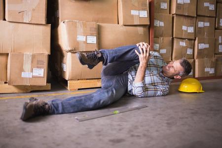 hard worker: Vista laterale del lavoratore di sesso maschile disteso sul pavimento in magazzino Archivio Fotografico