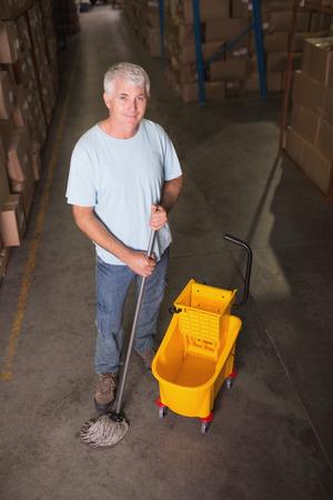 superintendent: Portrait of man moping warehouse floor