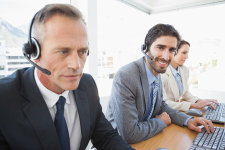 Business team working at the call center wearing headsets photo