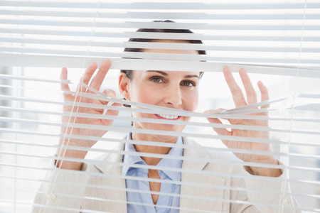 glancing: A woman glancing through some blinds in her office