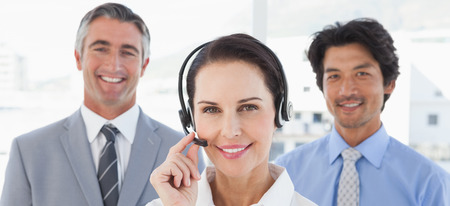 center agent: Businesswoman wearing her headset with co workers behind her Stock Photo