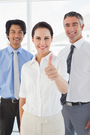 Smiling businesswoman giving a thumbs up with co workers photo