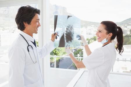 Smiling doctors holding an x ray at work photo