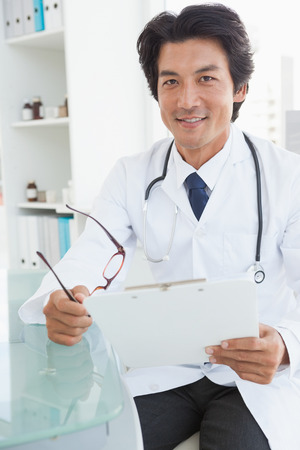 Happy doctor sitting at his desk holding glasses photo