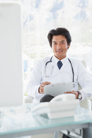 Smiling doctor reading over notes in his office photo