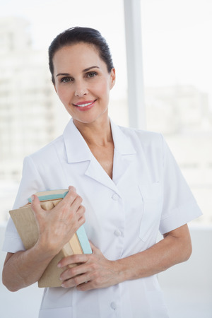 Smiling doctor holding medical books in an office Stock Photo