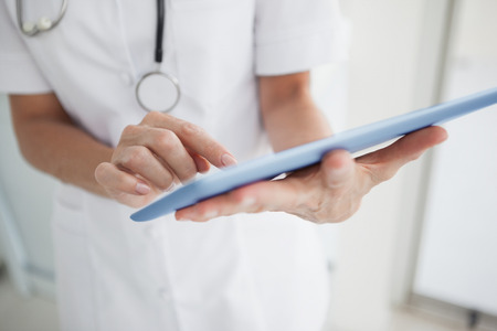 scrolling: Doctor scrolling on her tablet at work