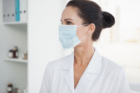 Doctor wearing a surgical mask at a hospital office