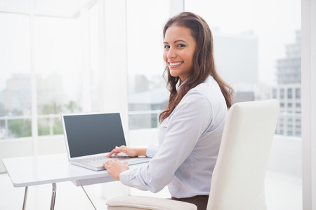 Smiling businesswoman using laptop at her desk in her office photo