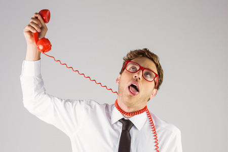 strangling: Geeky businessman strangling himself with telephone on grey background