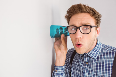 eavesdropper: Geeky businessman eavesdropping with cup on grey background Stock Photo