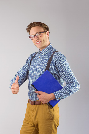 geeky: Geeky student holding a notebook on grey background