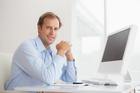 Casual businessman smiling at camera at his desk in his office photo