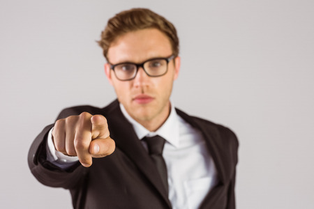 Young serious businessman pointing at camera on grey background photo