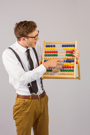 Geeky businessman using an abacus on grey background