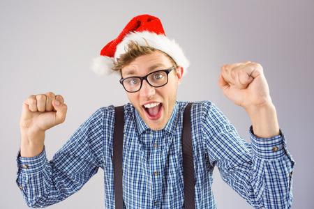 wearing santa hat: Geeky hipster wearing santa hat on grey background