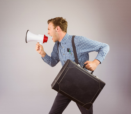 businessman using a megaphone: Geeky hipster shouting through megaphone on grey background