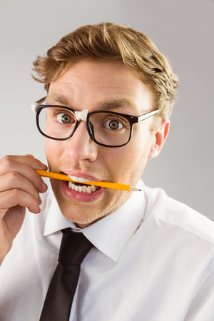 Geeky businessman biting a pencil on grey background photo