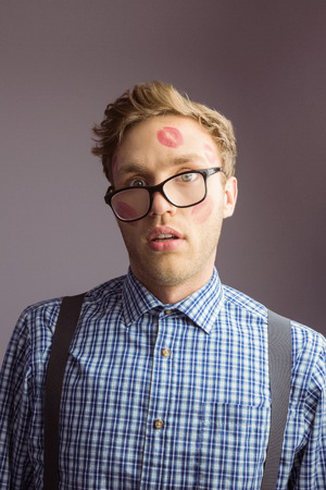 lustful: Geeky hipster covered in kisses on grey background