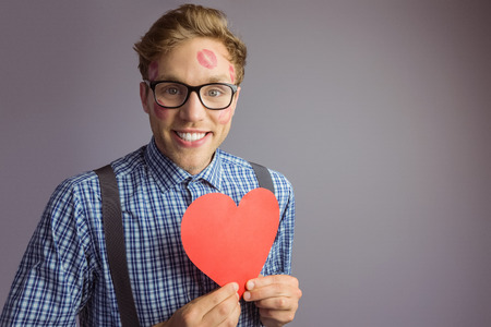 Geeky hipster covered in kisses on grey background photo
