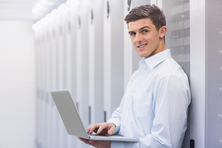 data center: Smiling technician typing on his notebook and leaning against a tower in a large data center