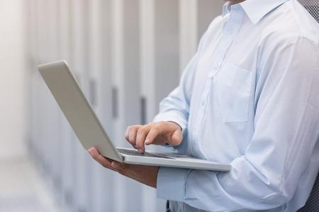 centro de computo: Mediados de secci�n de una tipificaci�n t�cnico en su cuaderno y apoyado contra una torre en un centro de datos de gran tama�o Foto de archivo