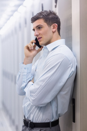 Young technician on the phone leaning against a tower in a large data center photo