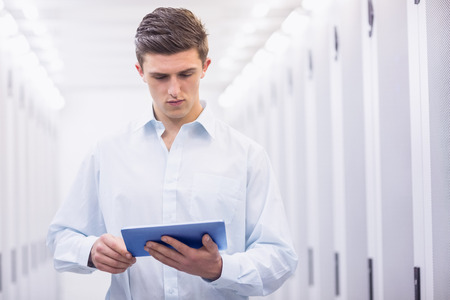 Concentrating young technician working with his tablet in a server room photo