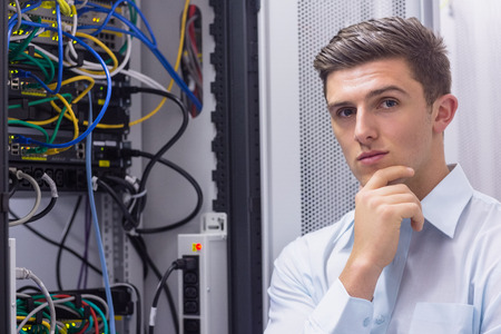 Thoughtful young technician with arms crossed next to the server case in a large data center photo