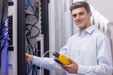 maintaining: Technician smiling at camera while fixing server in large data center