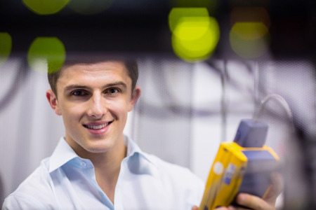 analyzer: Happy technician using digital cable analyzer on server in large data center Stock Photo