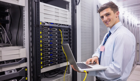 digital data: Smiling technician using laptop while analysing server in large data center Stock Photo
