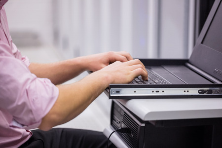 data center: Close up of technician sitting using laptop to diagnose servers in large data center Stock Photo